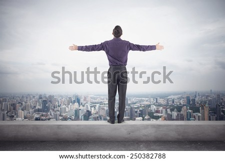 Confident businessman in a purple shirt and trausers standing on the edge of the roof with his hands on the sides in front of the magnificent view of the city. - stock photo