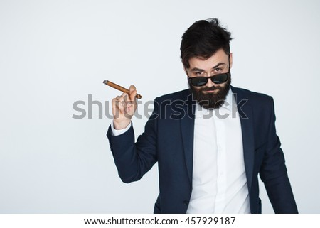 Confident businessman in black suit with beard looking at camera while smoking a cigar isolated on white