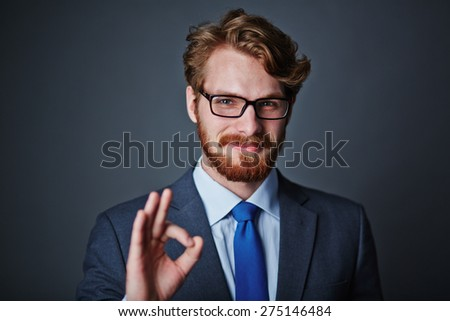 Confident businessman in eyeglasses showing okay sign - stock photo