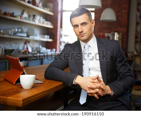 Confident businessman in formal cloths drinking coffee and reading news in the kitchen - stock photo