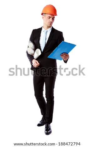 Confident businessman in helmet reading construction plan over white background - stock photo
