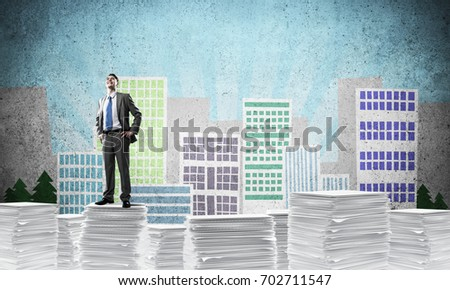 Confident businessman in suit standing on pile of documents with drawn cityscape background. Mixed media.
