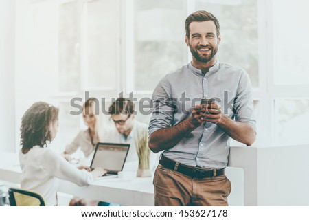 Confident businessman. Joyful young man holding mobile phone and looking at camera while his colleagues working in the background