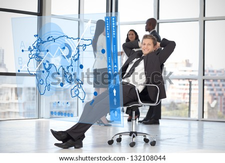 Confident businessman looking at blue map diagram interface with colleagues behind him