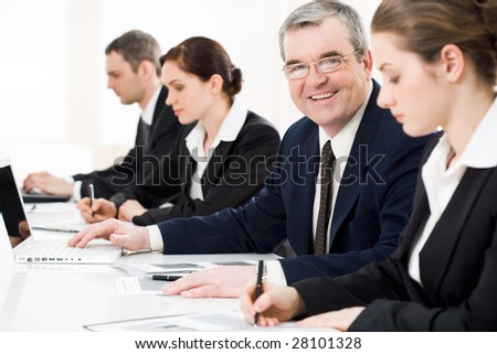 Confident businessman looking at camera among his employees at briefing