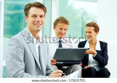 Confident businessman looking at camera at background of his communicating colleagues