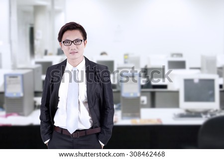 Confident businessman looking at camera in the office - stock photo