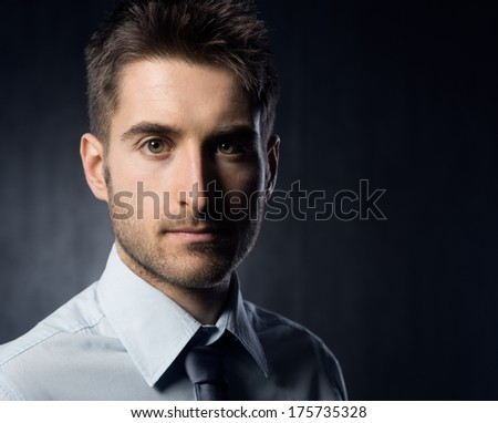 Confident businessman looking at camera on dark background.