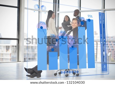 Confident businessman looking at futuristic chart interface with colleagues behind him - stock photo