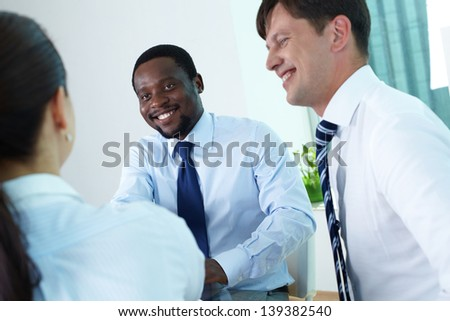 Confident businessman looking at his partner speaking in office - stock photo