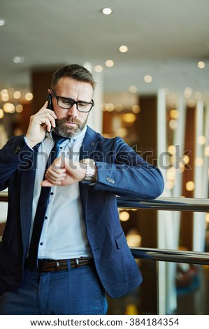 Confident businessman looking at his watch while talking on the phone