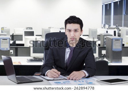 Confident businessman looking at the camera while sitting in the office and work on the table