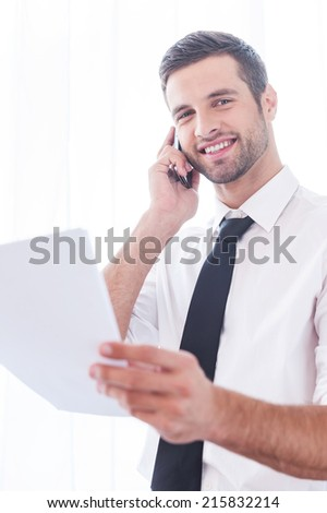 Confident businessman. Low angle view of cheerful young man in shirt and tie talking on the mobile phone and holding document - stock photo