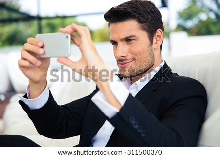 Confident businessman making selfie photo on smartphone in restaurant - stock photo