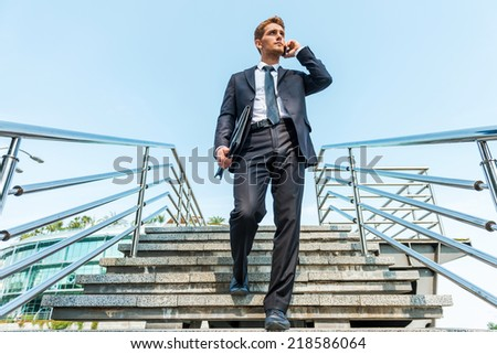 Confident businessman on the phone. Low angle view of confident young man in formalwear talking on the mobile phone while moving down by staircase - stock photo