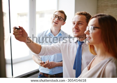 Confident businessman pointing at information on board while his colleagues listening to him