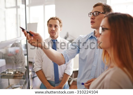 Confident businessman pointing at information on board with his colleagues near by - stock photo
