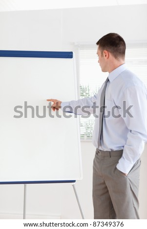 Confident businessman pointing at the middle of a flip chart - stock photo