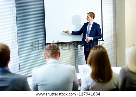 Confident businessman pointing at whiteboard while making speech at conference - stock photo