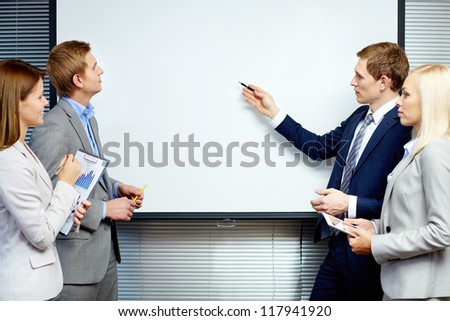 Confident businessman pointing at whiteboard while making speech at meeting - stock photo