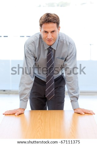 Confident businessman posing leaning on a table in an office - stock photo