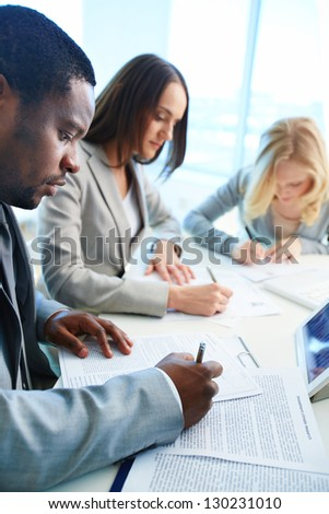 Confident businessman signing papers with his two employees working on background - stock photo