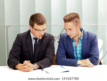 Confident businessman signing the contract in front of his partner