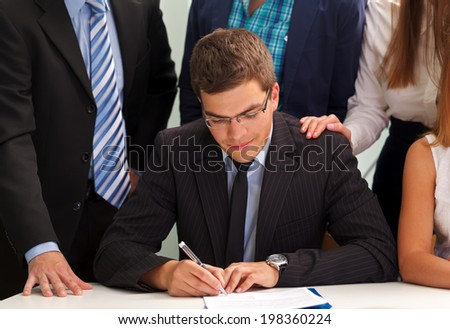 Confident businessman signing the contract in front of his team - stock photo