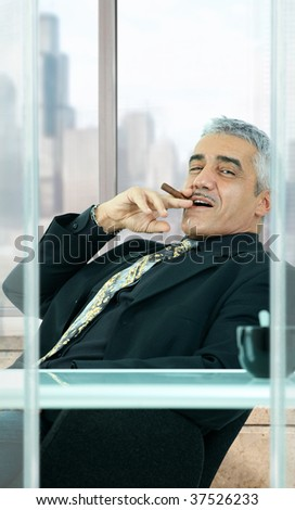 Confident businessman sitting at desk in front of office windows, leaning back, smoking cigar.