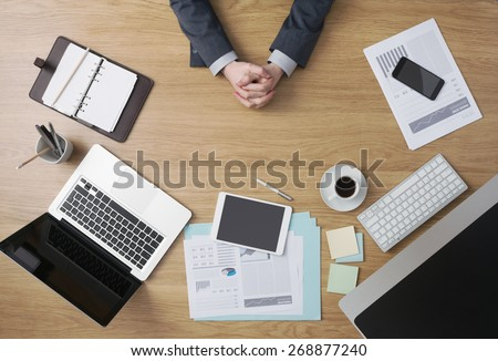 Confident businessman sitting at his office desk with hands clasped, paperwork and computers around, hands detail top view - stock photo