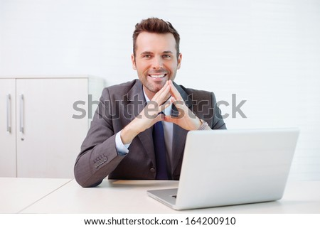 Confident businessman sitting at the desk - stock photo