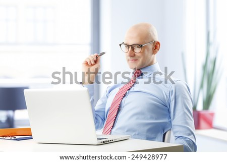 Confident businessman sitting in front of computer and thinking to solve the problem.