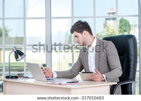 Confident businessman sitting in the office and dial number on cell phone. Businessman making successful business.