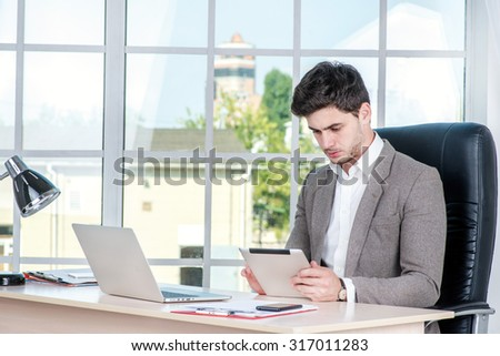 Confident businessman sitting in the office and working on laptop. Businessman making successful business and holding tablet.