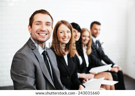 Confident businessman sitting with business partners in background - stock photo