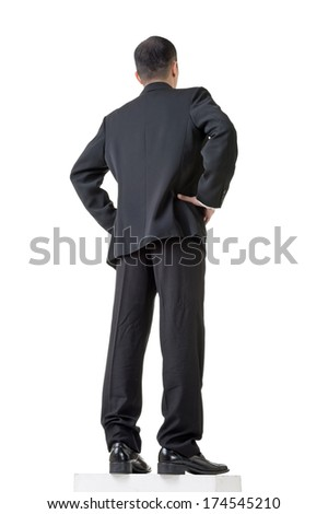 Confident businessman standing and looking into distance, low angle and rear view and full length portrait isolated against white background.