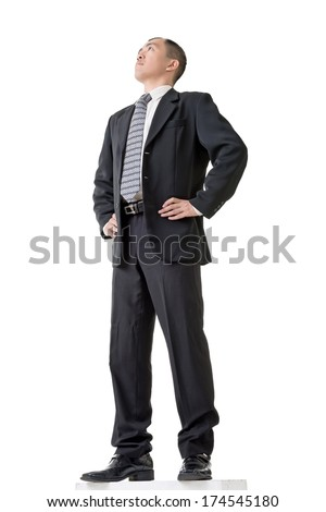 Confident businessman standing and looking into distance, low angle view and full length portrait isolated against white background.