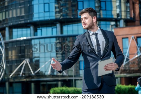 Confident businessman standing in the street and holding a tablet in hand client meetings on the street and shakes hands