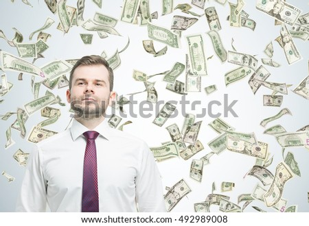 Confident businessman standing under dollar bill rain in room with gray walls. Concept of successful business. Mockup. Toned image