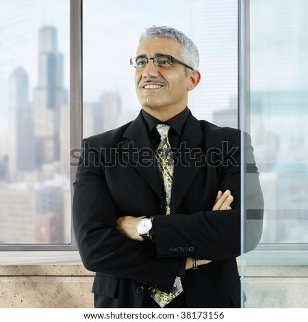 Confident businessman standing with arms crossed in front of office windows, smiling.