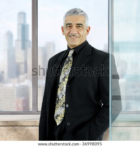 Confident businessman standing with hand in pocket in front of office windows, smiling.
