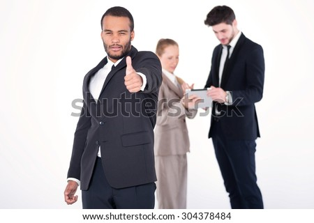 Confident businessman. Successful African businessman standing and shows his thumb up while his colleagues are working on a tablet in the background on a gray background - stock photo