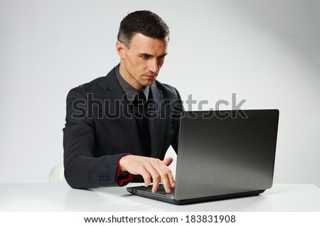 Confident businessman typing on the laptop isolated on a gray background