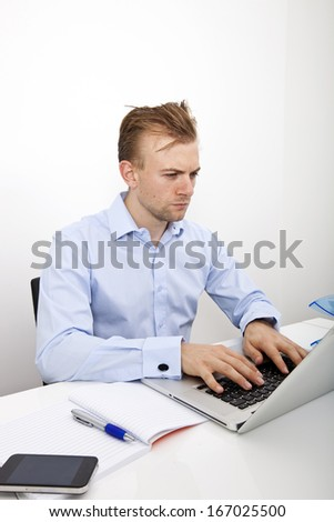 Confident businessman using laptop at desk in office