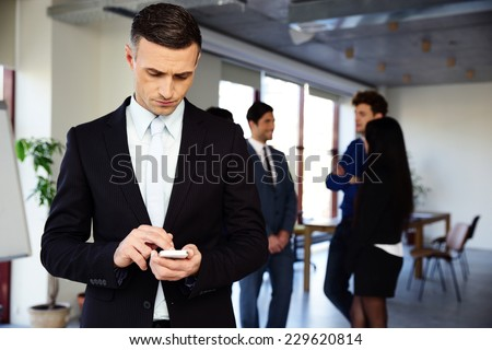 Confident businessman using smartphone in front of a colleagues - stock photo