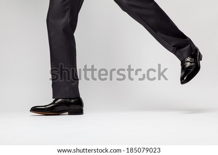 Confident businessman walking - closeup of legs on gray background