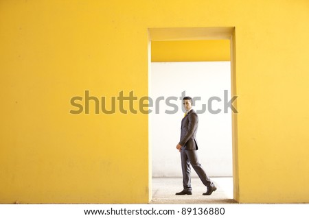 Confident businessman walking next to a yellow wall