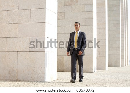 Confident businessman walking next to his office building