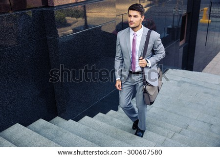 Confident businessman walking on stairs outdoors - stock photo