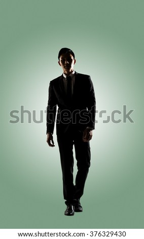 Confident businessman walking, silhouette portrait isolated - stock photo